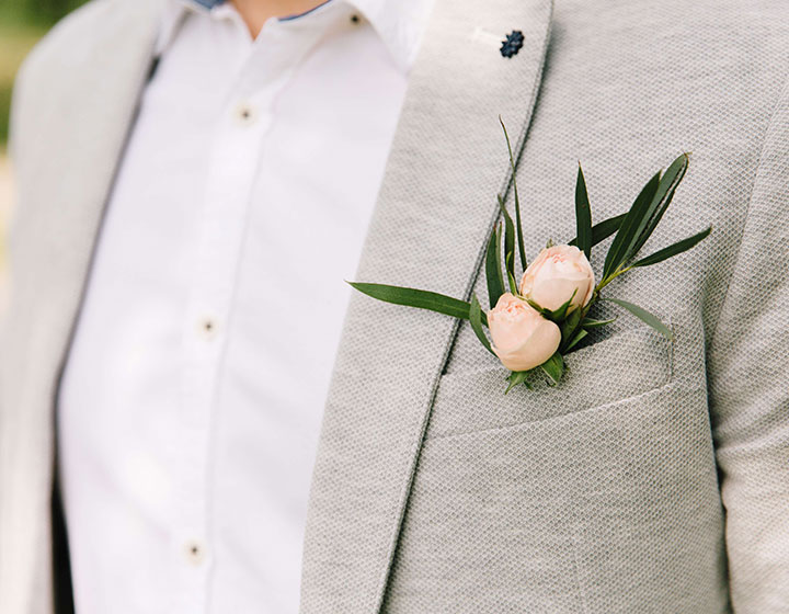man in gray suit with pink flower
